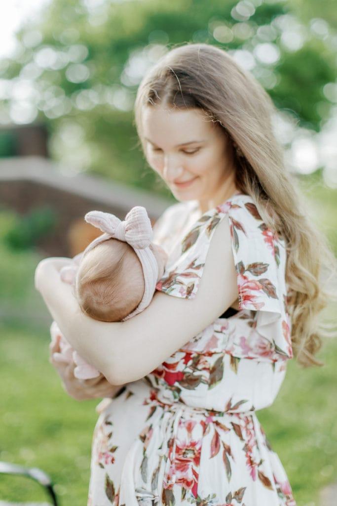 mother cradling her newborn baby girl: outdoor newborn session