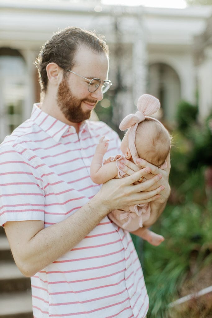 Father holding his newborn baby girl in mellon park: outdoor newborn session