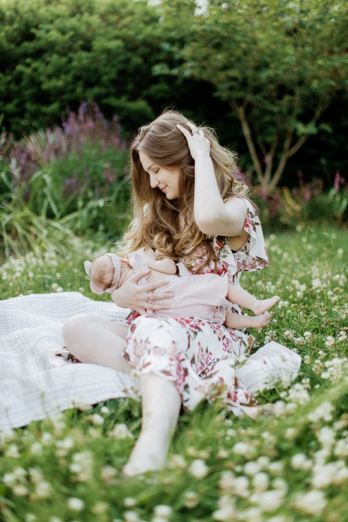 Young mother wearing a light pink floral dress breastfeeds her newborn baby girl while sitting in the grass: outdoor newborn session