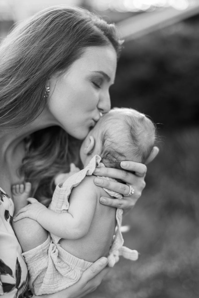 black and white image of mother kissing her newborn baby in an english garden: outdoor newborn session