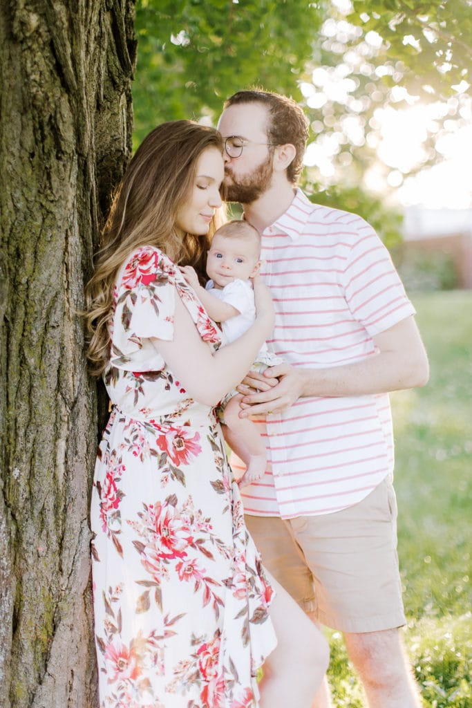 family hugging and holding their newborn baby leaning on a tree: outdoor newborn session