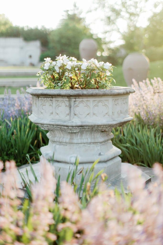 White flowers in stone urn inside english garden at mellon park