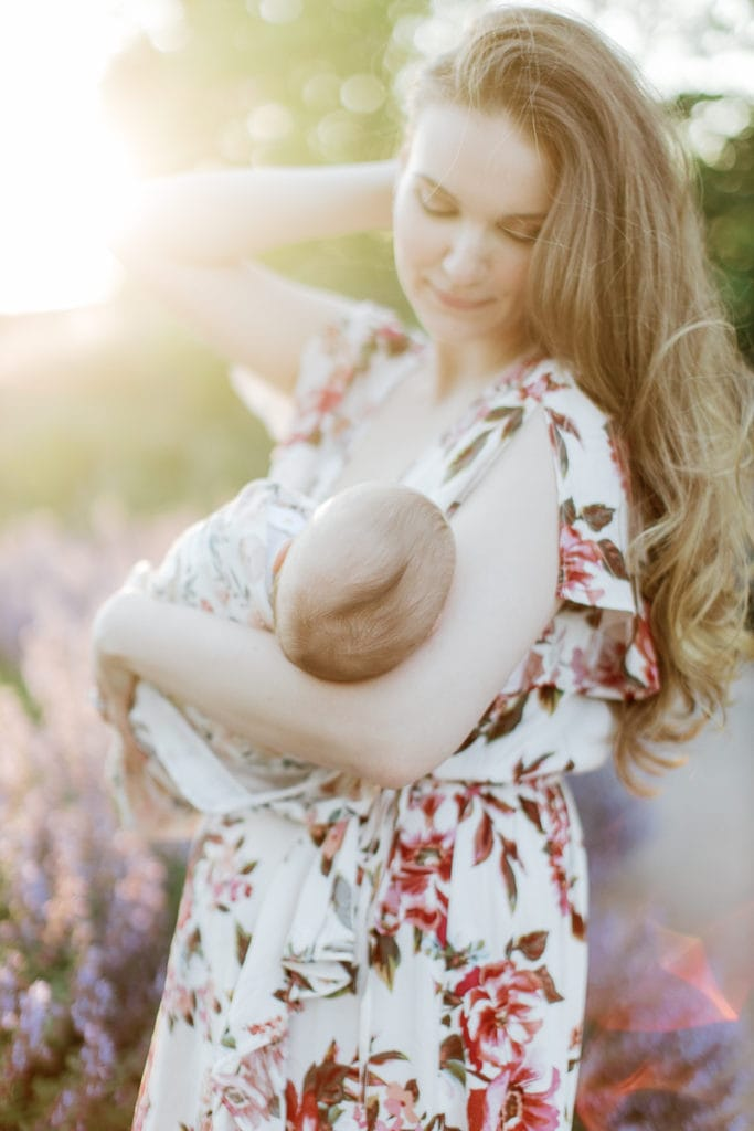 New mother holding her newborn while walking through lavender: outdoor newborn session