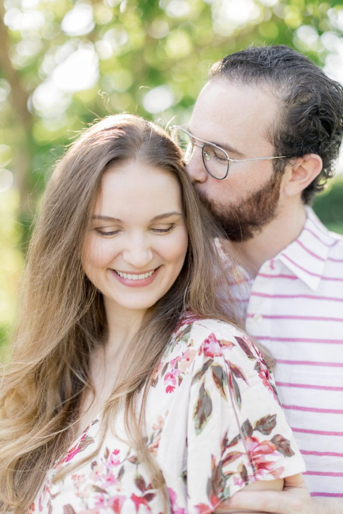 man kissing wife on the head while smiling and laughing: outdoor newborn session