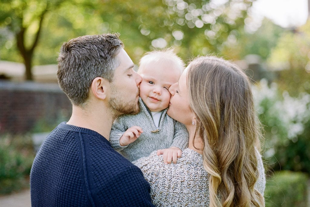 Parents kissing baby's cheeks during family photo session with Lauren Renee