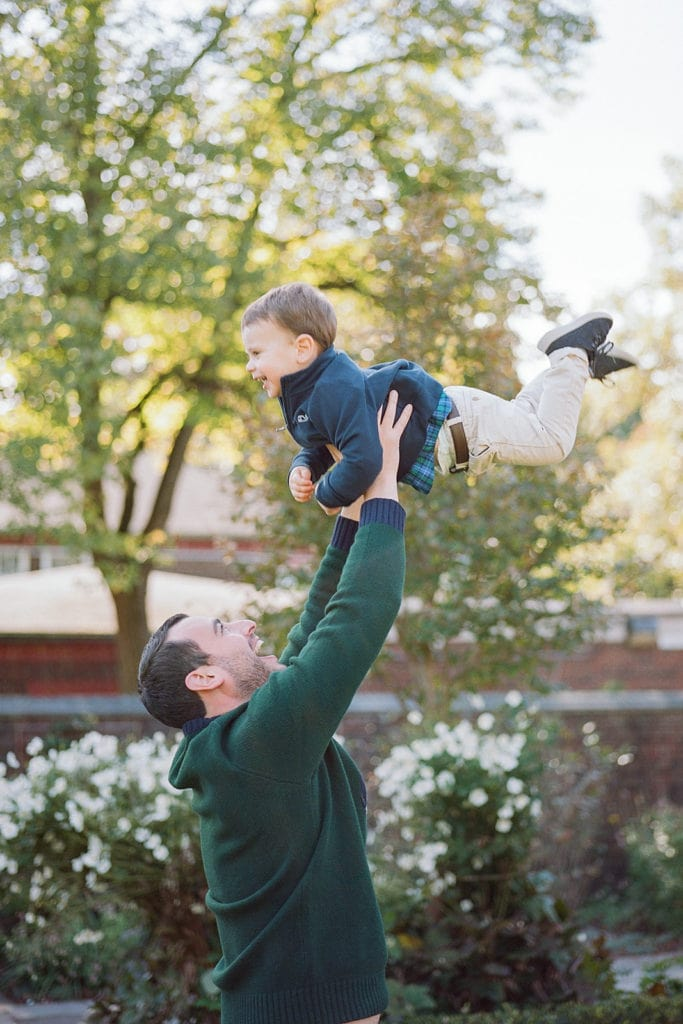 Dad lifting up son during family photos by Lauren Renee