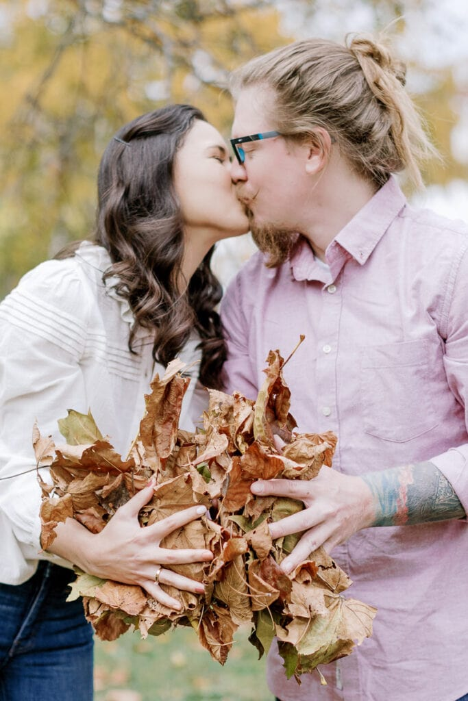 Husband and wife kissing while holding a bundle of fall leaves