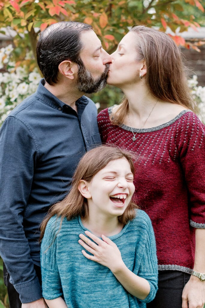 Little girl laughing as her parents kiss