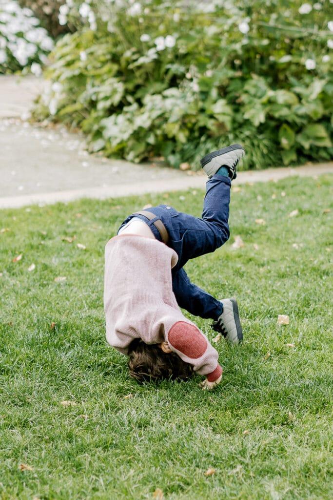 Little boy doing a somersault in Mellon Park