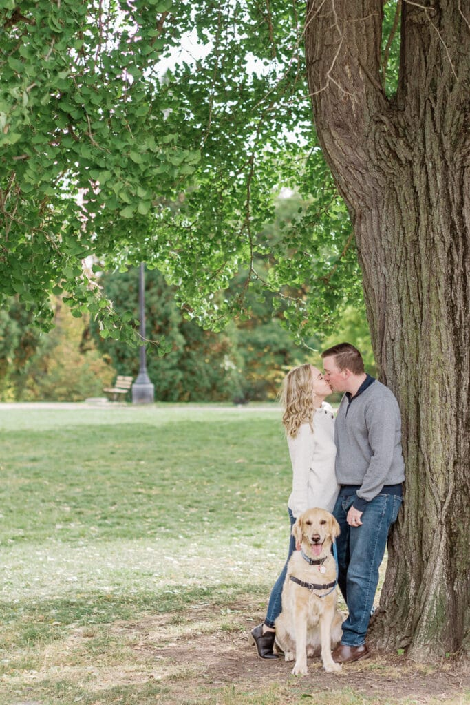 Couple kissing against a tree holding their dog