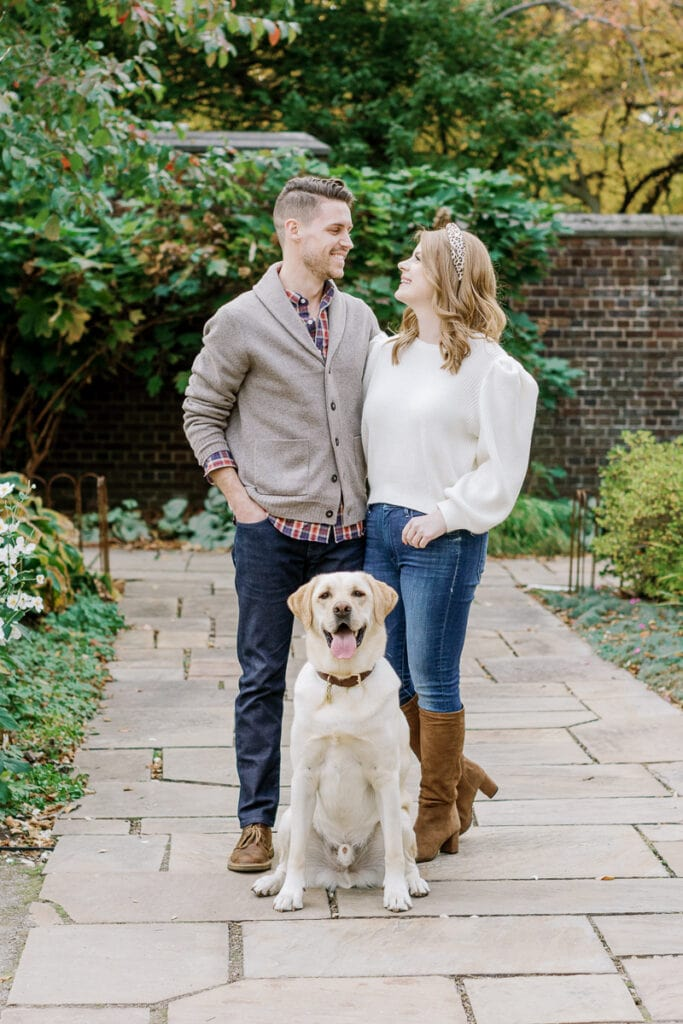 Couple looking at one another with their dog posing in between them