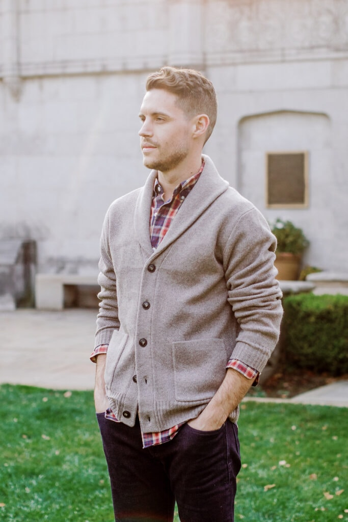 Man wearing a plaid shirt and button down cardigan