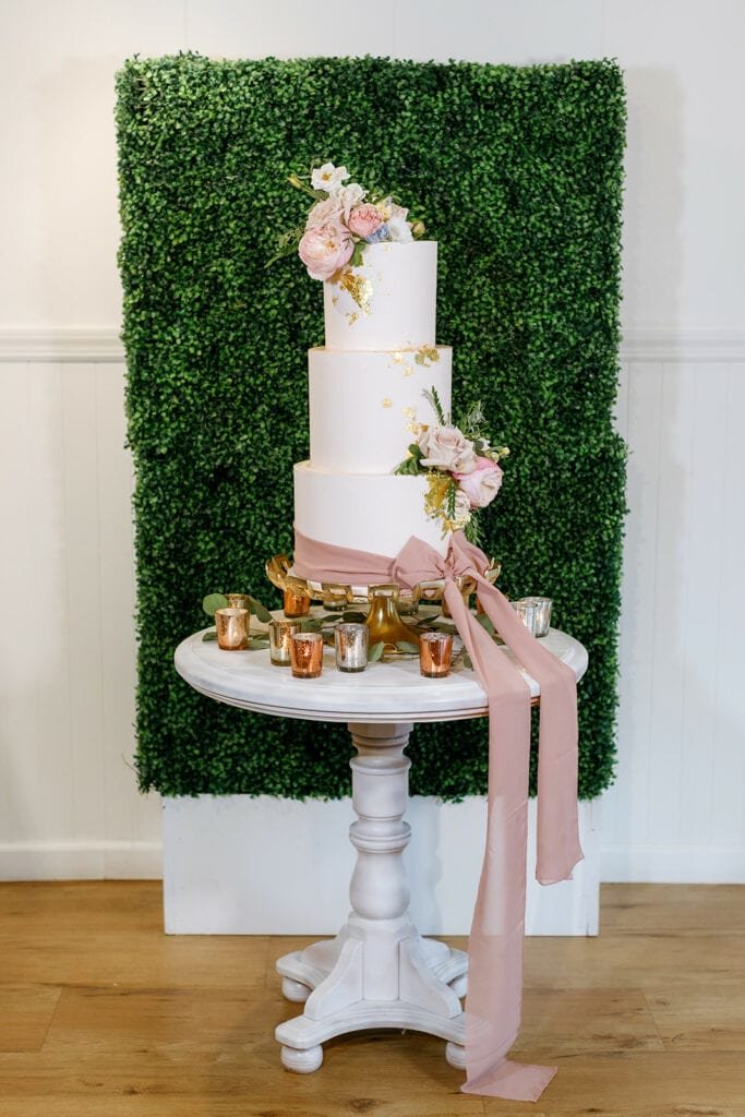 Luxurious pink and white wedding cake with flowers and a bow