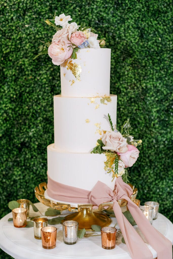 Pink and white wedding cake with gold foil and a pink bow