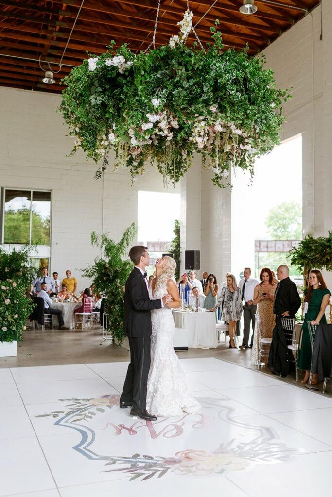 First dance under greenery floral wedding chandelier