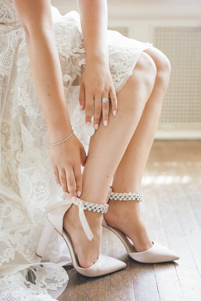 Bride putting on nude pointed toe wedding shoes