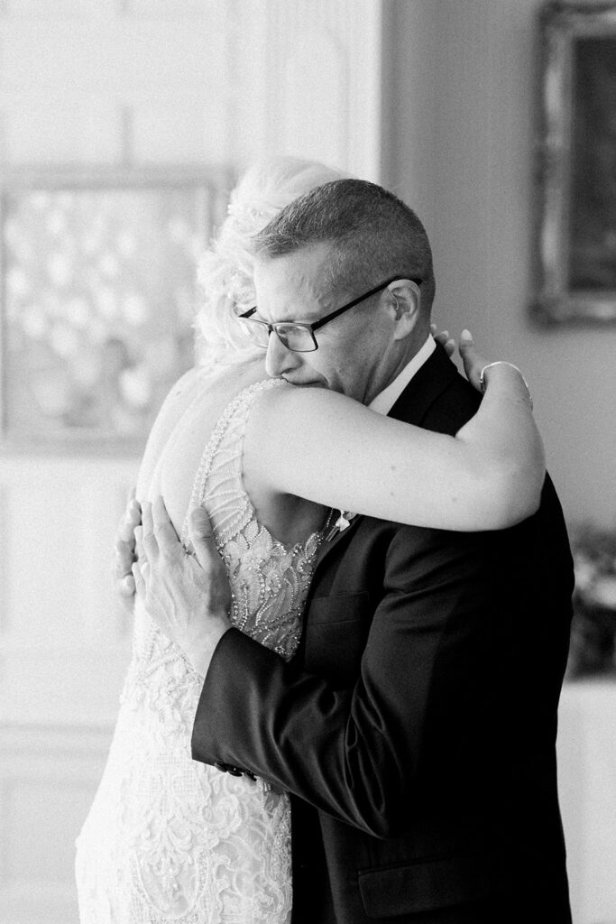 Bride and father of the bride hugging