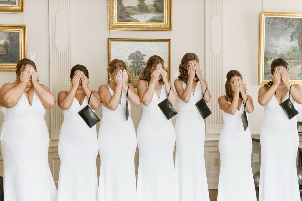Bridesmaids in white bridesmaid dresses during bride's first look
