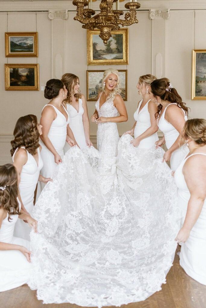 Bridesmaids posing with bride's wedding dress
