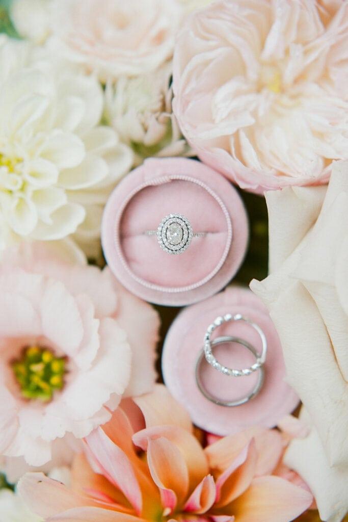 Wedding and engagement rings in circular pink ring box