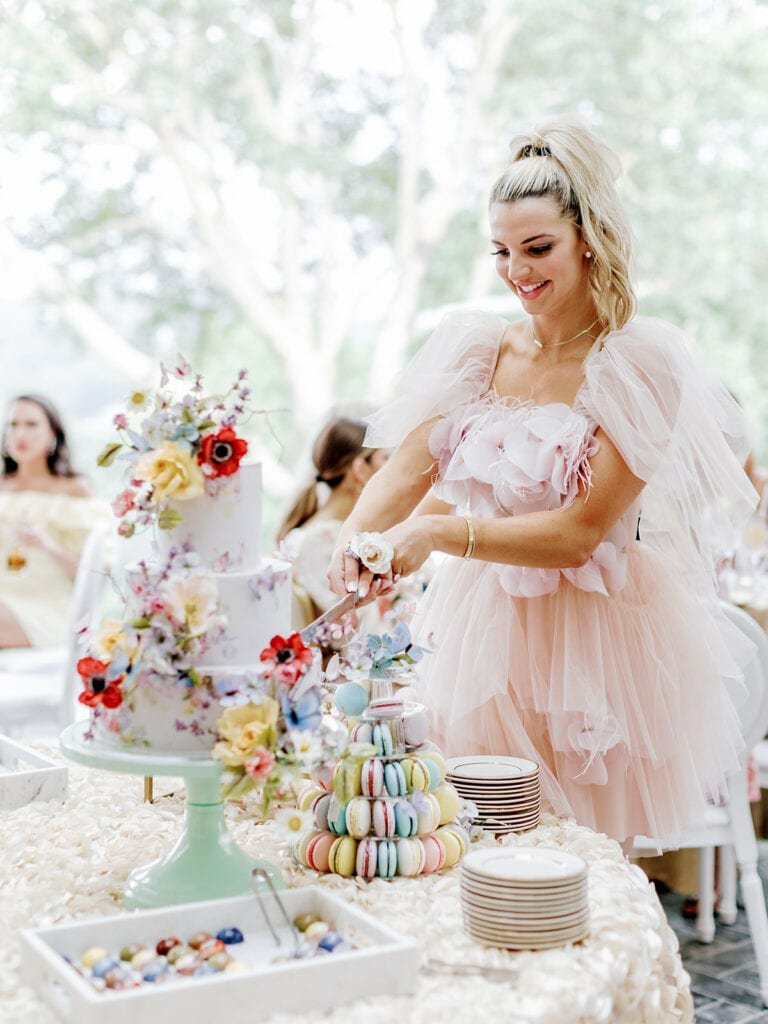 Blogger Sincerely Ryleigh cutting into bridal shower cake from Alex Robba Cake