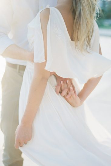 close up of couple holding hands during engagement photos