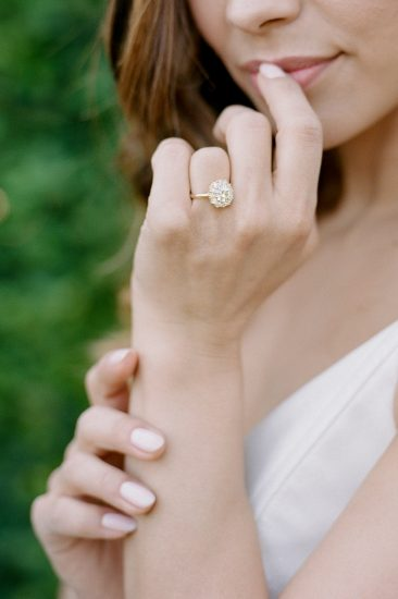 close up of a bride's hand wearing a trumpet and horn vintage ring
