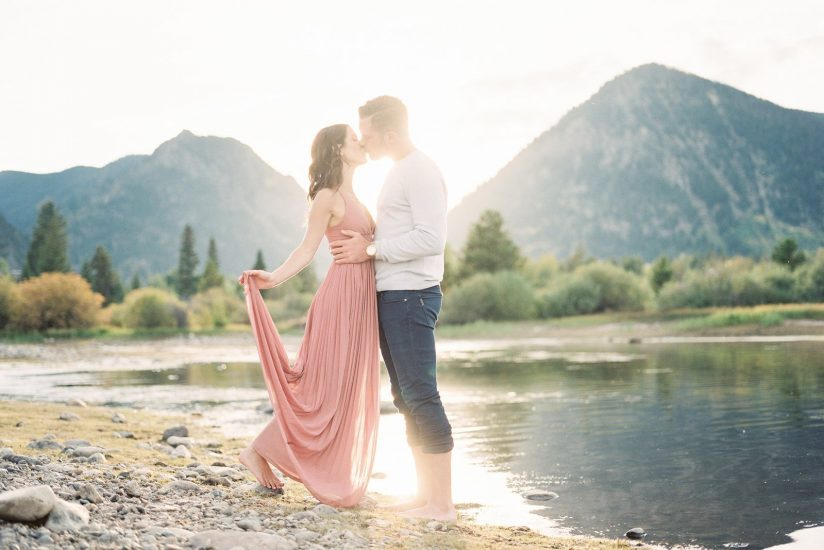Man and woman kiss during sunset over lake Dillon Colorado
