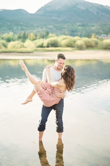 man carrying woman standing in Lake Dillon