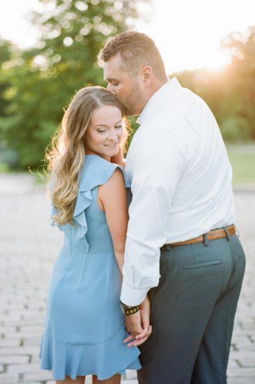 man kissing woman on the head woman wearing a blue ruffled dress