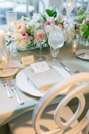 Reception table set up with sage and pink flowers with white wash claire chairs