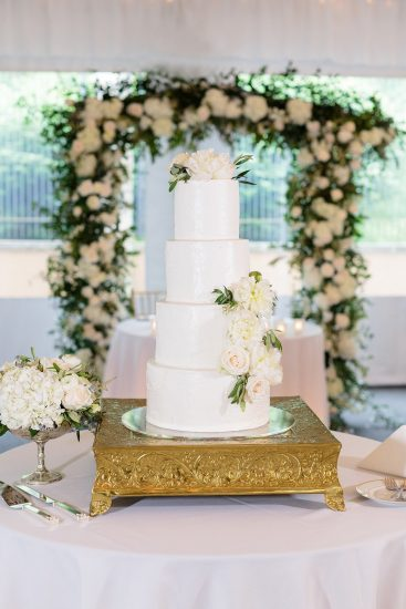 white wedding cake with white flowers in front of a white flower arch