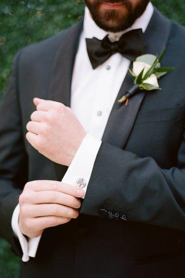 groom fixing his cufflinks