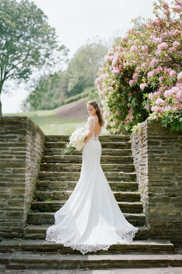 Bride standing on cobblestone staircase holding bouquet