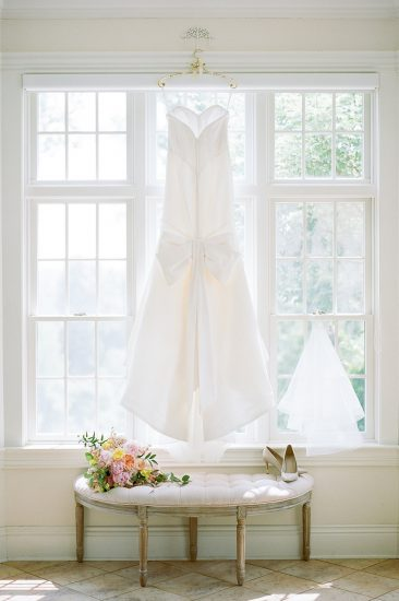 zac posen dress hanging in window with bouquet and veil