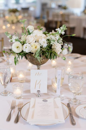 table setting with calligraphy table numbers and champagne flutes with escort cards