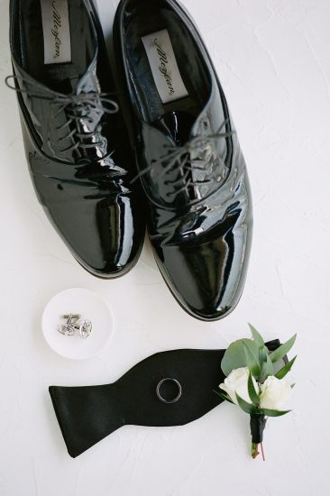 groom's details shoes cufflinks and bow tie and boutonnière