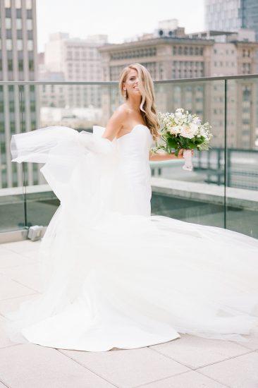 bride dancing in her wedding dress on the roof of hotel monaco