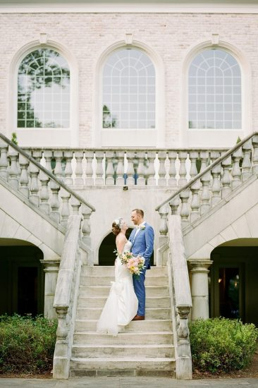 bride and groom standing on staircase in front of mansion with arch windows