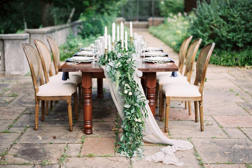 English garden table set up with cane back chairs and silk and willow table runner and greenery