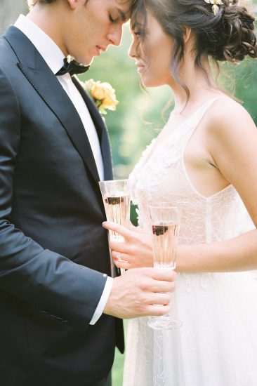 couple holding champagne flutes with black berries