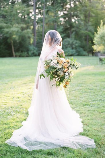 Bridal portrait with veil and bouquet at sunset in the grass