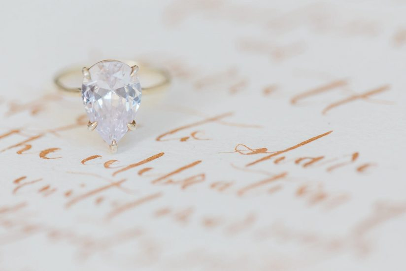 susie saltzman pear shaped solitaire diamond engagement ring on calligraphy note