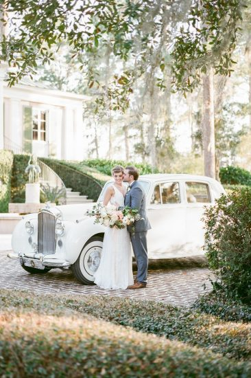 Bride and Groom standing in front of a white Rolls Royce