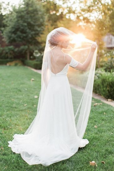 bride standing in grass wearing a wedding dress under her veil