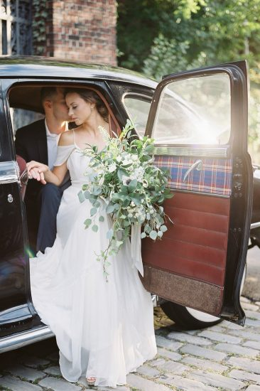 couple sitting in a vintage Chrysler with large white bouquet