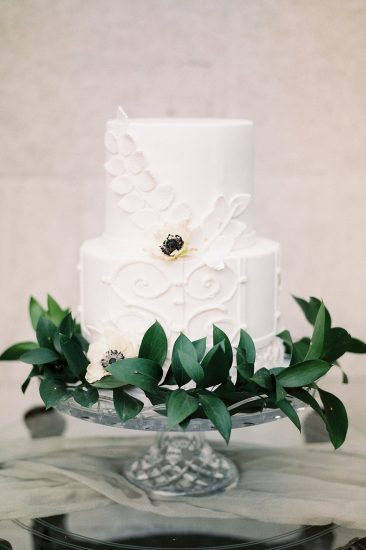 white two tiered cake with green garland