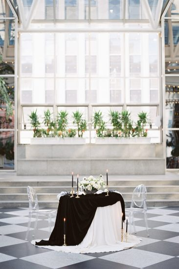 sweetheart table set up with acrylic chairs and black and white velvet table clothes at the PPG wintergarden