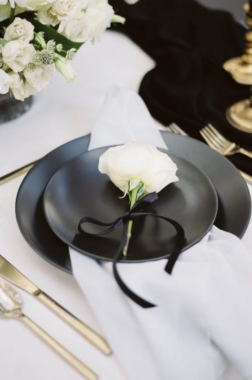 close up details of black matte plates with a rose on top and gold silverware