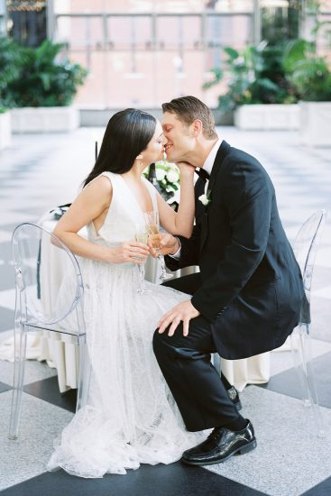 Couple sitting at their sweet heart table while kissing